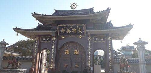 九華山大興善寺正門,圖片中間是寺廟的門樓,兩旁有石獅子雕塑