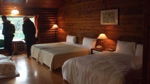 南元農場木屋內部臥室圖,有兩張雙人床與幾盞黃色燈具