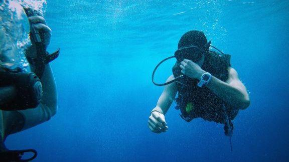手錶防水等級示意圖,圖中有個潛水員配戴一支白色手錶,地點在海裡