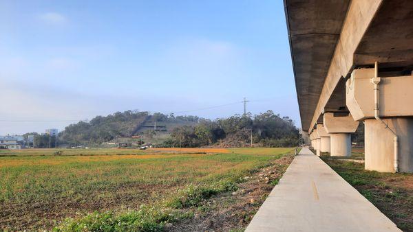 圖片左邊中間是錦山公園、右側有高鐵高架的軌道,軌道下方有條炎山自行車道的水泥道路,左下方則是綠色與橘黃色交雜的農田