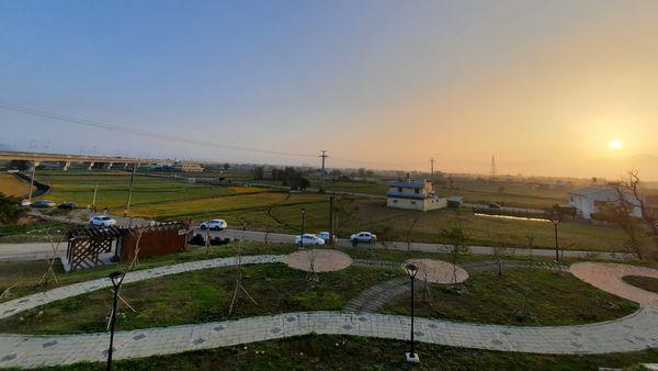 從錦山公園遊樂區往下方看的優美景緻,由上方有夕陽,中間有綠色黃色農田,下方有白色石磚步道