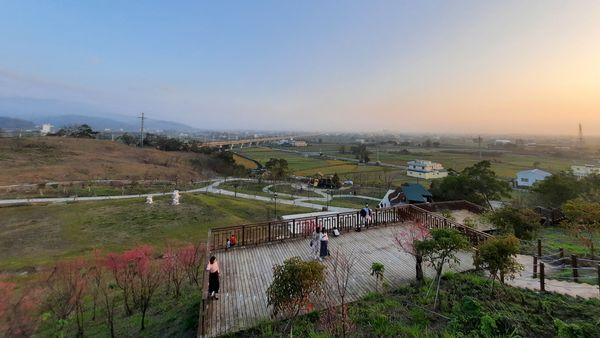 從更高的木製平台往下望的景觀,可看到下方的一木製平台,左側的粉色櫻花與上方的綠色黃色農田